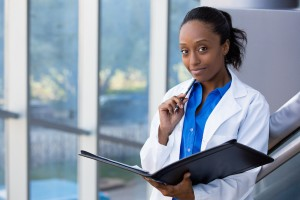 Closeup headshot portrait of friendly smiling confident female doctor healthcare professional with labcoat holding pen to face and holding notebook pad. Isolated hospital clinic background.